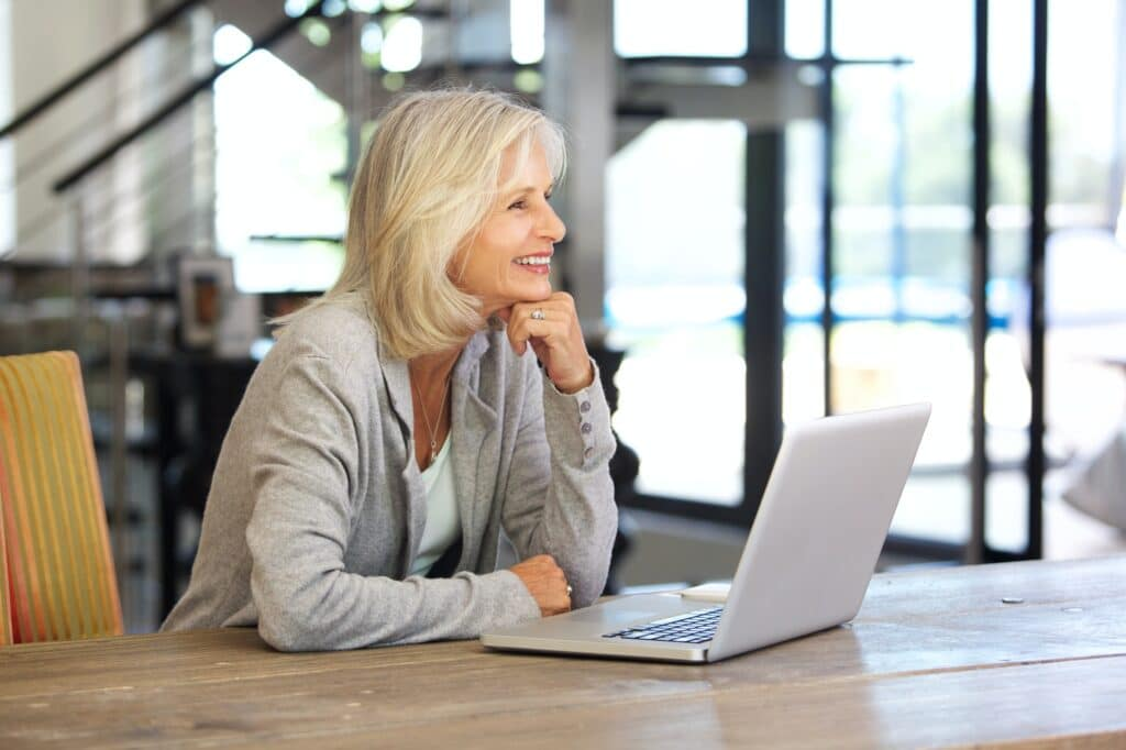 smiling older woman working laptop computer indoors
